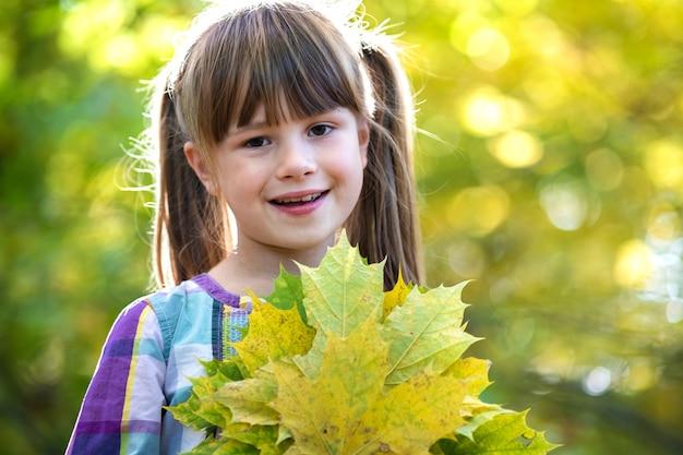 Портрет счастливой милой девушки ребенка держа пук упаденного дерева выходит в лес осени. положительный женский ребенк наслаждаясь теплым днем в парке падения.