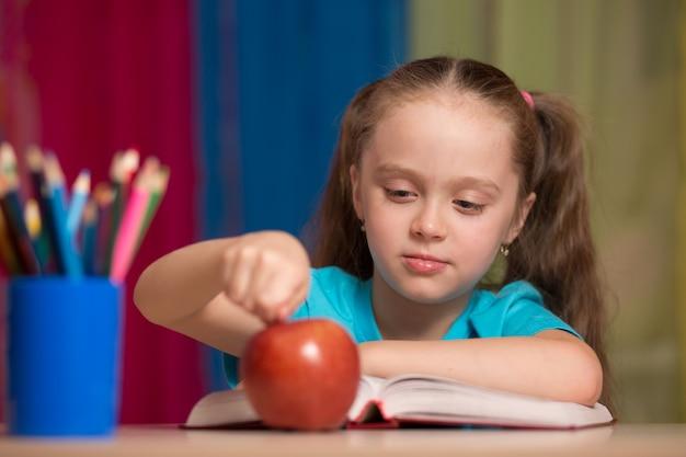教室で赤いリンゴを保持している幸せなかわいい女の子の肖像画