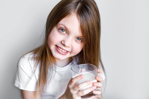 美しい笑顔でミルクのグラスを持つ幸せなかわいい女の子の肖像画
