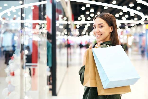 モールの店の陳列ケースに立っている肩に買い物袋を持つ幸せなかわいい女の子の肖像画