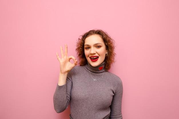 灰色のセーターと巻き毛の幸せなきれいな女性の肖像画