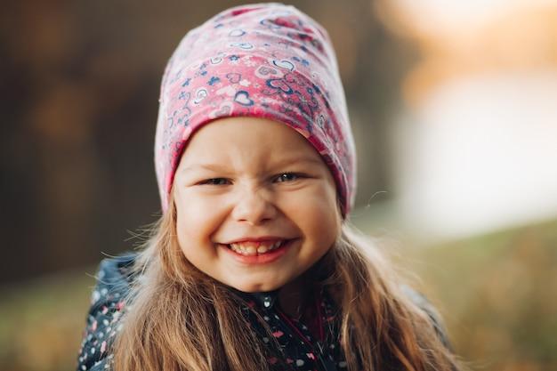 ジャケットと帽子が公園で時間を過ごす幸せなかわいい女の子の肖像画