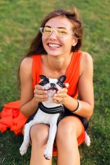 Портрет счастливой красивой женщины, сидящей на траве в летнем парке, держащей собаку бостон-терьера, улыбающейся позитивным настроением, в оранжевом платье, модном стиле, солнцезащитных очках, играющей с домашним животным, веселой