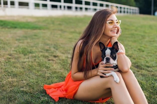 サマーパークの芝生に座って、ボストンテリア犬を抱いて、ポジティブな気分を笑顔、オレンジ色のドレス、流行のスタイル、サングラス、ペットと遊ぶ幸せなきれいな女性の肖像画