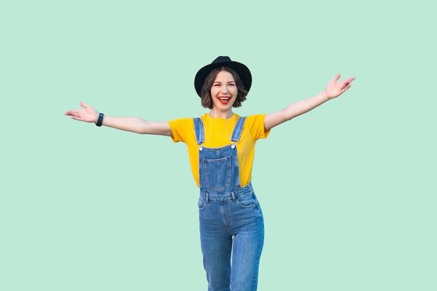 青いデニムのオーバーオール、黄色いシャツ、腕を上げて立っている黒い帽子、歯を見せる笑顔でカメラを見ている幸せなかわいい若い女の子の肖像画。薄緑の背景に分離されたスタジオショット。