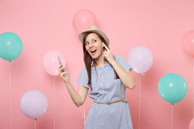 Портрет счастливой милой молодой женщины в соломенной летней шляпе и голубом платье с мобильным телефоном и наушниками, слушая музыку на пастельном розовом фоне с красочными воздушными шарами. праздник дня рождения.