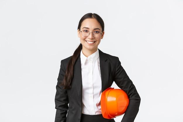幸せな職業の女性アジア建設マネージャー、ヘルメットを保持し、カメラに笑みを浮かべて、検査のために建物エリアに入る、白い背景のビジネススーツのエンジニアの肖像画
