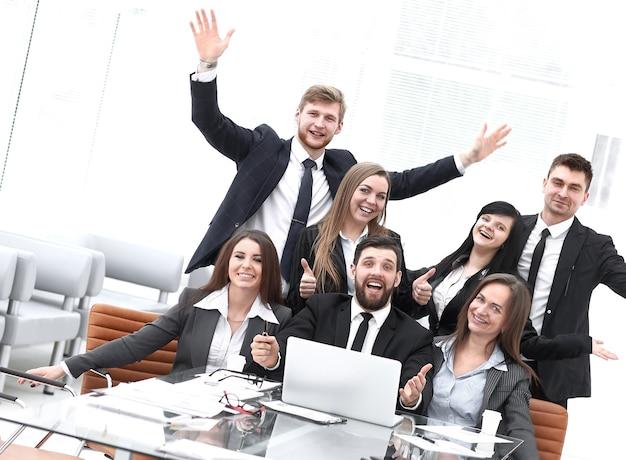 Портрет счастливой профессиональной бизнес-команды возле стола