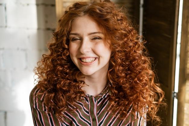 Портрет счастливой рыжей вьющейся молодой женщины возле окна, улыбаясь крупным планом