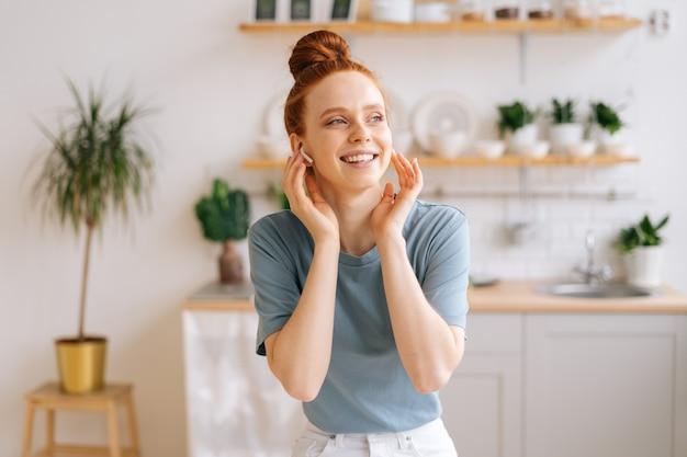 책상에 앉아 있는 동안 무선 헤드폰으로 음악을 듣는 행복한 빨간 머리 젊은 여성의 초상화