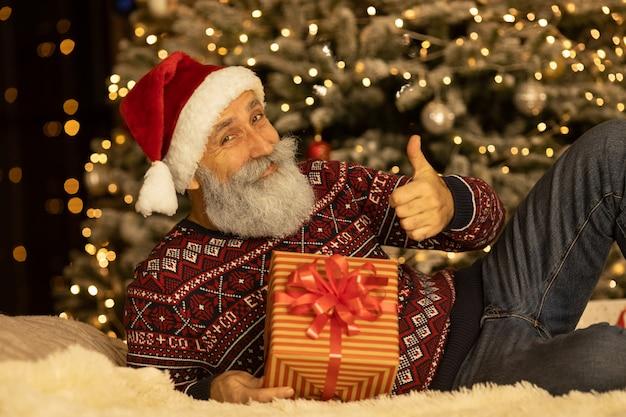 自宅のクリスマスツリーの近くの彼の部屋で幸せなサンタクロースの肖像画。