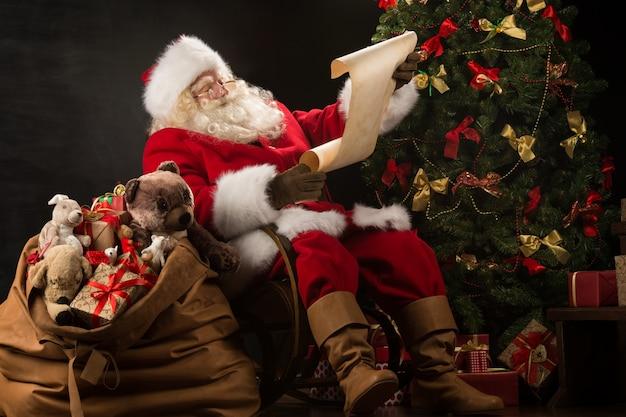 Портрет счастливого санта-клауса, читающего рождественское письмо или список желаний