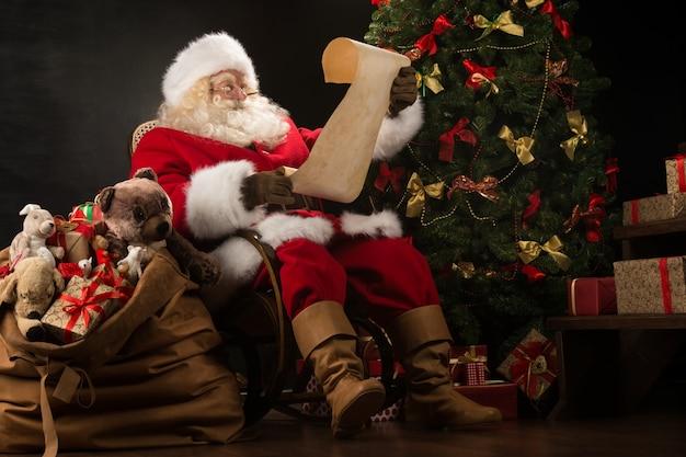 Портрет счастливого санта-клауса, читающего рождественское письмо