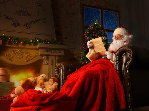 Портрет счастливого санта-клауса, сидящего в своей комнате дома возле елки и читающего рождественское письмо или список желаний.