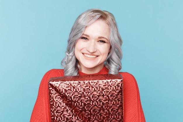 幸せなサンタの女性の肖像画は、分離されたギフトボックスを抱擁します。
