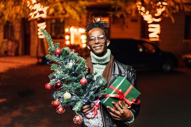 Портрет счастливого довольного афроамериканца, стоящего с елкой и подарком в руках и улыбающегося