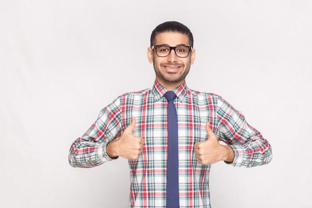 カラフルな市松模様のシャツ、青いネクタイ、親指を立てて歯を見せる笑顔で立っている黒い眼鏡で幸せ満足のハンサムなひげを生やした実業家の肖像画。スタジオショット、灰色の背景に分離。