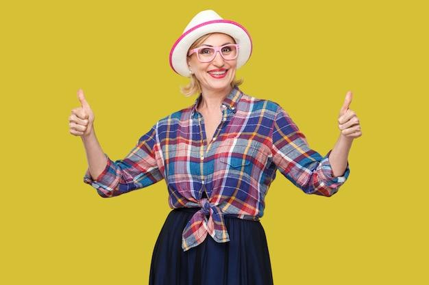カジュアルなスタイルで幸せな満足のモダンなスタイリッシュな成熟した女性の肖像画、帽子と眼鏡が立っている、親指を立てて、歯を見せる笑顔でカメラを見てください。黄色の背景に分離された屋内スタジオショット。