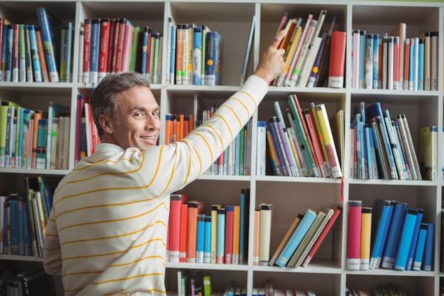 図書館で本を選択する幸せな学校の先生の肖像画