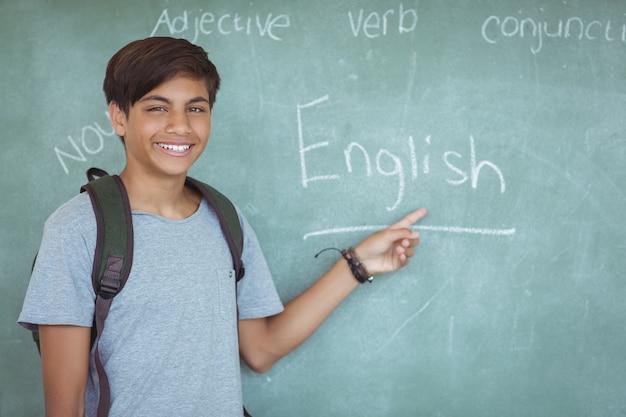 Портрет счастливого школьника, указывая на классную доску в классе