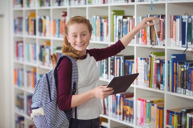 図書館で本を選択する幸せな女子高生の肖像画