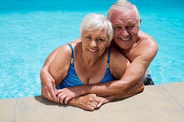 수영장에서 서로 껴 안은 행복 한 노인 커플의 초상화