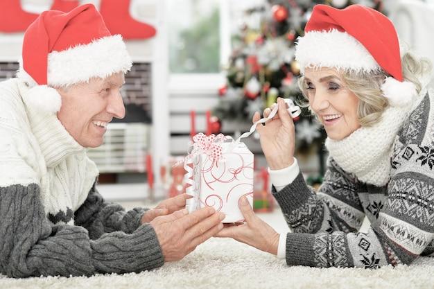 선물과 함께 산타 모자에 행복 한 수석 커플의 초상화