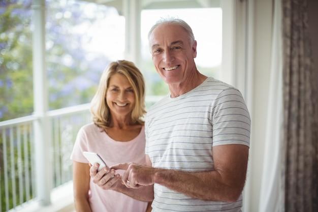 Портрет счастливой старшей пары, стоящей на балконе с мобильным телефоном