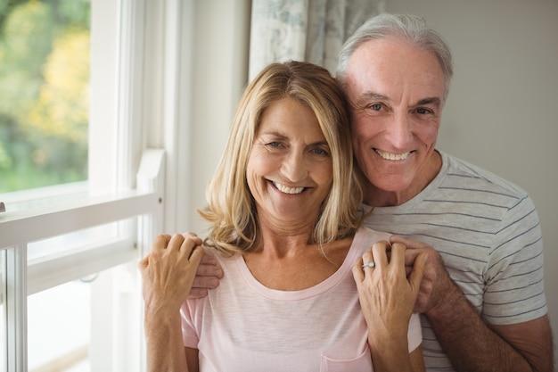 Портрет счастливой старшей пары, стоящей рядом с окном