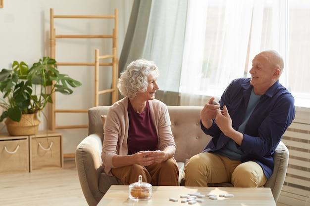 Портрет счастливой старшей пары эмоционально разговаривает, сидя на диване в уютном домашнем интерьере, освещенном солнечным светом