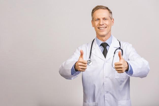 灰色の壁を越えて笑って幸せな年配の男性医師の肖像画。いいぞ。