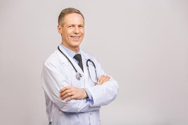 腕を組んで灰色の壁を越えて笑って幸せな年配の男性医師の肖像画。