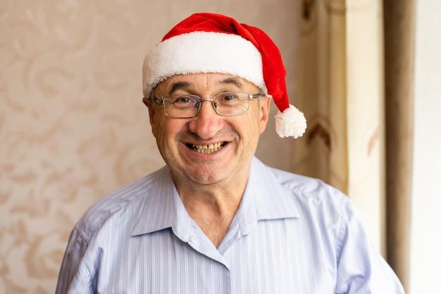 Портрет счастливого старшего человека в шляпе санты, готовящейся к рождеству