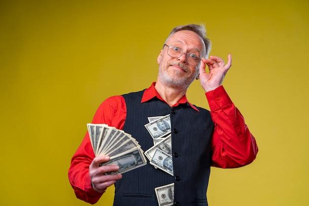 手にお金を持って笑顔で幸せなシニア老ビジネスマンの肖像画