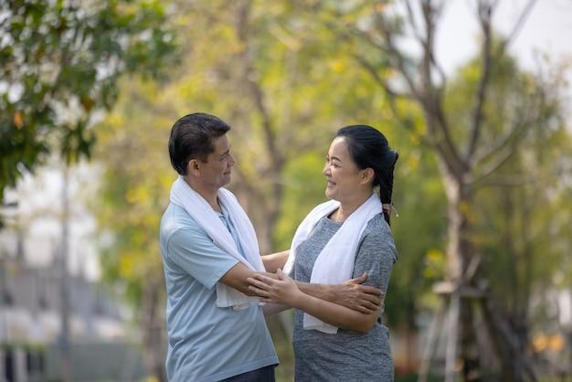 屋外で走っている幸せなシニアスポーツカップルの肖像画