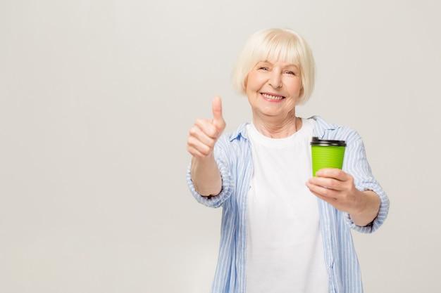 Портрет счастливой старшей женщины выпивая кофе изолированный на белой предпосылке. недурно.