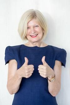 Портрет счастливый старший женщина показывает палец вверх