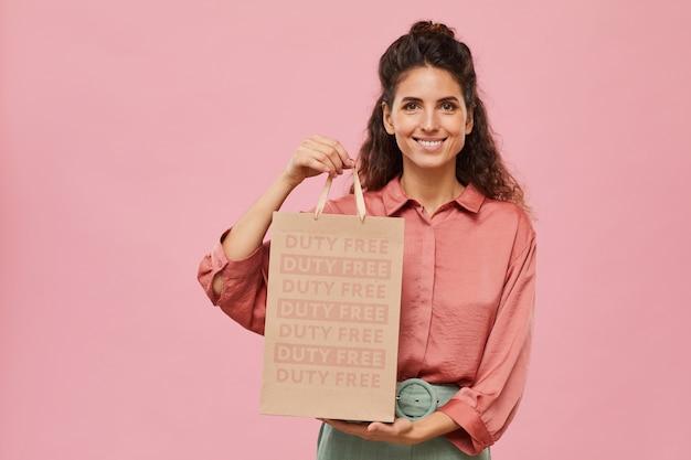 Портрет счастливого шопоголика с вьющимися волосами, держащего бумажный пакет и улыбающегося на розовом фоне
