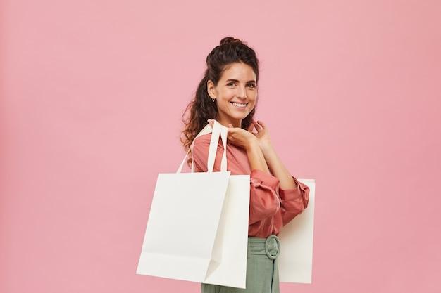 Портрет счастливого шопоголика с сумками, улыбающимися на розовом фоне