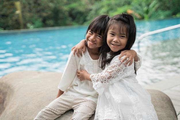 スイミングプールの背景に描かれた幸せな姉妹の肖像画