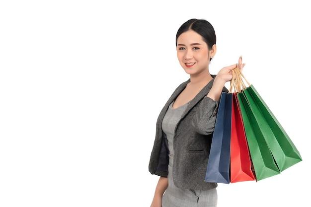 幸せな笑顔のアジアの女性の肖像画は、白い背景の上の買い物袋を保持します。