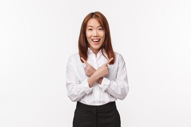 Портрет счастливой улыбающейся азиатской женщины, офисного работника в белой рубашке, указывая пальцами влево и вправо на два варианта, несколько вариантов, спрашивая совета, выглядят бодро на белой стене