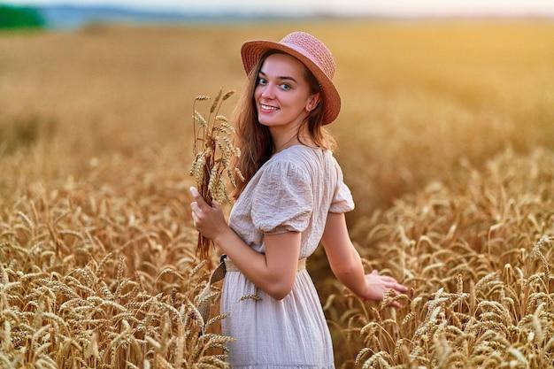 Портрет счастливой улыбающейся привлекательной милой свободной молодой женщины в шляпе и платье, стоящей в золотисто-желтом пшеничном поле и наслаждающейся прекрасной жизнью в момент свободы в летнее время