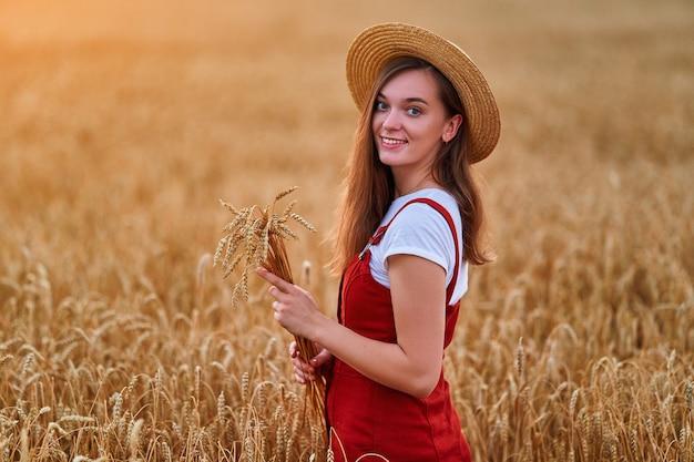 Портрет счастливой улыбающейся привлекательной милой свободной молодой женщины в соломенной шляпе и джинсовой ткани, стоящей в золотисто-желтом пшеничном поле и наслаждающейся прекрасной жизнью в момент свободы в летнее время