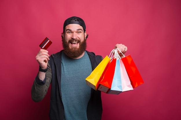 Портрет счастливого улыбающегося бородатого мужчины с сумками и кредитной картой