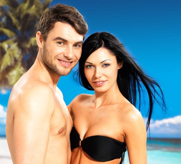 熱帯のビーチで恋に幸せな笑顔の美しいカップルの肖像画