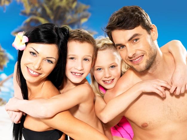 熱帯のビーチで2人の子供と幸せな笑顔の美しい家族の肖像画