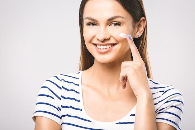 クリームを適用して触れる幸せな笑顔の美しい若い女性の肖像画