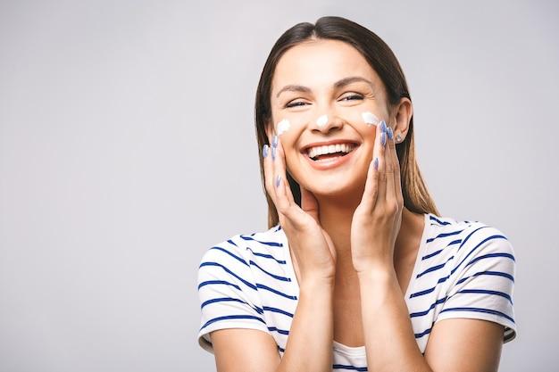 クリームを適用肌に触れる幸せな笑顔の美しい若い女性の肖像画