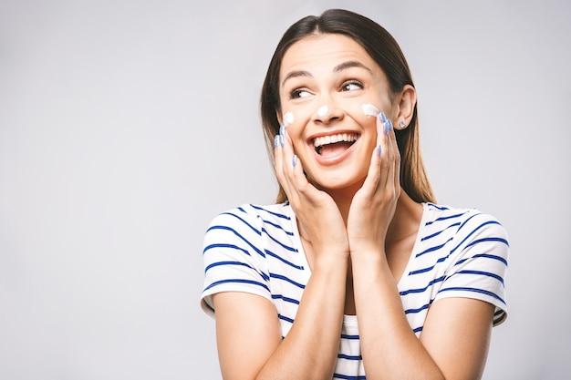 肌に触れたり、クリームを適用して幸せな笑顔の美しい若い女性の肖像画